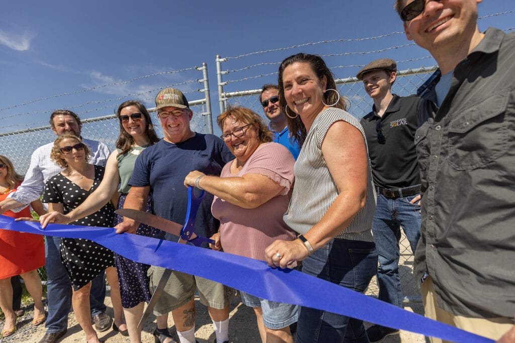 blue ribbon cutting with employees smiling